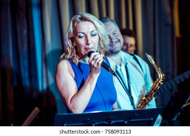 A woman of 40-45 years old, a singer, sings into a microphone. Vocal instrumental group on stage.