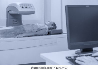 Woman in 40s undergoing open mri with doctor supervising.