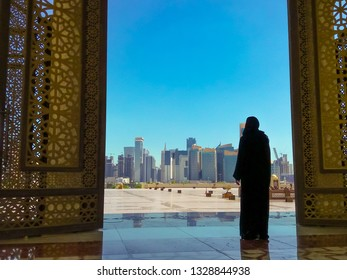Woman with abaya dress looks at views of modern skyscrapers of Doha West Bay skyline outdoors State Grand Mosque in Doha, Qatar, Middle East, Arabian Peninsula. Sunny day with blue sky.
