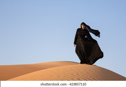 A woman in abaya in sanddunes in Liwa Desert, Aby Dhabi, UAE