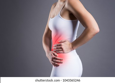 Woman with abdominal pain on gray background