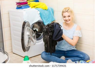 Woman about to do laundry. Having big pile of dirty clothing sitting next to washing machine.