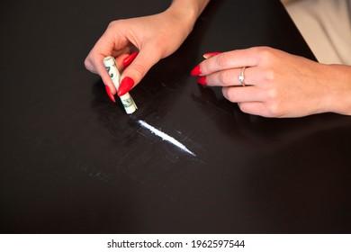 Frau steht kurz davor, eine Heroin- oder Kokainlinie mit Dollarschein zu schnuppern