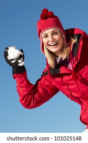 Woman About To Throw Snowball Wearing Warm Clothes On Ski Holiday In Mountains