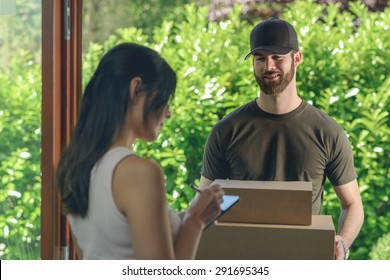 Woman accepting a delivery of two cardboard boxes with an order or gift signing the digital clipboard for the friendly smiling deliveryman on the doorstep