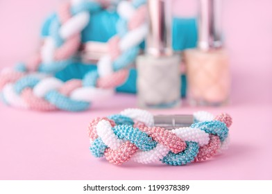 Woman  accessories: bracelet, nail polish, necklace,  on the pink background. Close up trendy fashion feminine background. Handmade beaded necklace and bracelet.  Beauty blog concept.