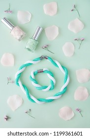 Woman  accessories: bracelet, necklace, nail polish with rose petals on the soft pastel green background. Flat lay, top view trendy fashion feminine background. Beauty blog concept.