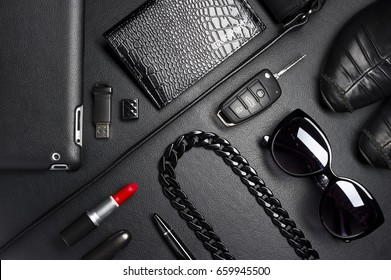 Woman accessories in business style, red lipstick, gadgets, shoes, jewelry, car key, bag, sunglasses and other luxury businesswoman attributes on leather black background, fashion industry, top view