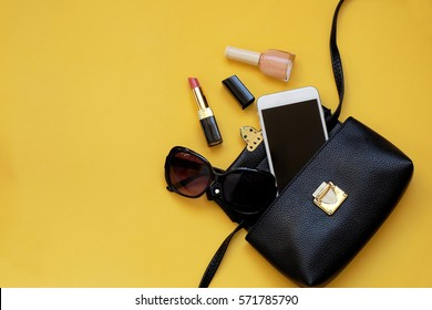 Woman Accessories lying flat on yellow paper background.