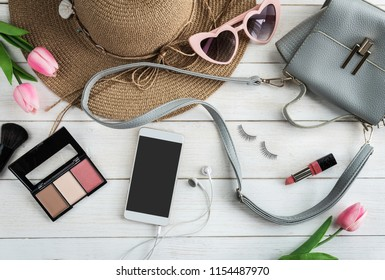 Woman accessories with make up, cosmetics, brushes and smart phone on white wooden background, Top view