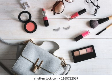 Woman accessories with make up, cosmetics, brushes on white wooden background, Top view