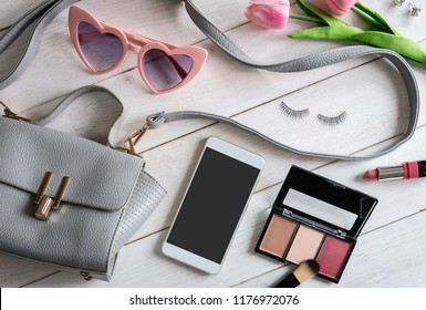 Woman accessories with make up, cosmetics, brush and smart phone on white wooden background, Top view