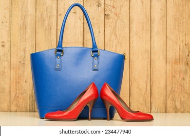Woman accessories on wood background, blue handbag and red stileto