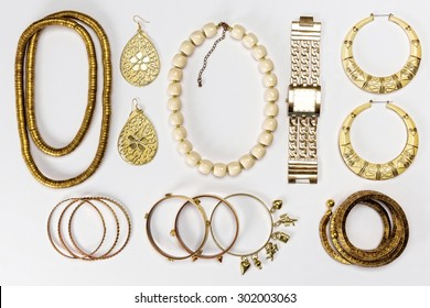 Woman accessories,gold and yellow,against white background.Top view.