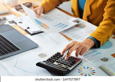 Woman accountant use calculator and computer with holding pen on - Shutterstock ID 1697077897