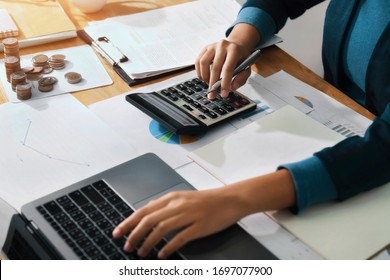 Woman accountant use calculator and computer on desk in office. Work for safe at home. finance and accounting concept