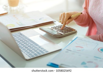 Woman accountant working on accounts in business analysis with graphs and document financial data report with laptop computer, planning tax payment at office, business concept.
