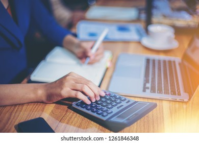 Woman accountant working using calculator for calculate financial report at the workplace.