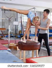Woman acrobat in bodysuit exercising action at vaulting hourse in gym,  man helping