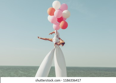Woman acrobat is spinning in the sky on balloons, she shows the performance.