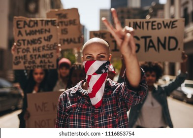 Woman activist with mouth covered gesturing peace sign during demonstration on rood. Group of females protesting with peace and silence.