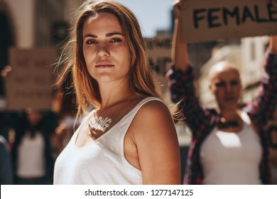 Woman activist with word strong written on her body standing outdoors. Strong young female activist protesting outdoors with her group in background.