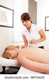 Woman acupuncturist stimulating needles on the back of a female patient.