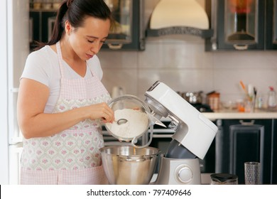 Woman add the flour for baking in the bowl of a food processor.