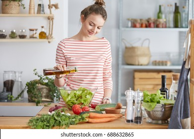 Woman adding olive oil to her healthy salad