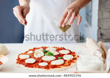 Woman adding oregano on raw pizza. Woman doing homemade pizza. Dressed in white pinny