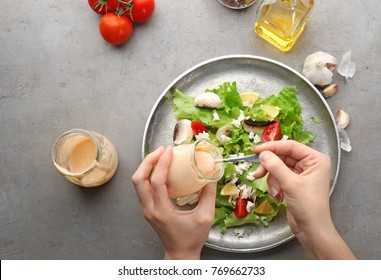 Woman adding ranch dressing to fresh salad on grey background