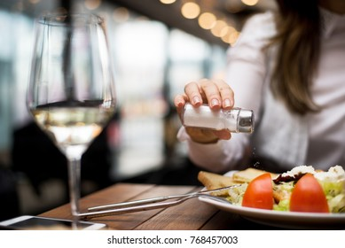 Woman adding salt to food in restaurant.