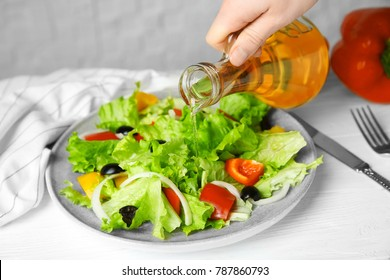 Woman adding tasty apple vinegar into salad with vegetables on plate