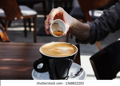 Woman adds cinnamon to cappuccino. A cup of cappuccino coffee on the table.
