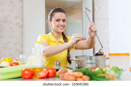 woman adds spice or salt in saucepan at kitchen