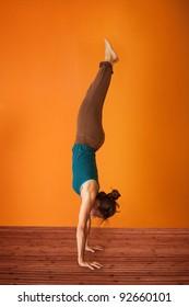 Woman in the Adho Mukha Vriksasana Yoga position