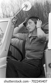 Woman adjusting her hat in convertible