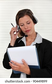 Woman adjusting her headset and holding a clipboard