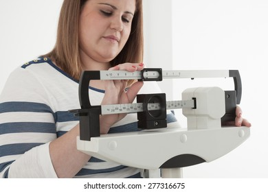 Woman adjusting a medical weight scale