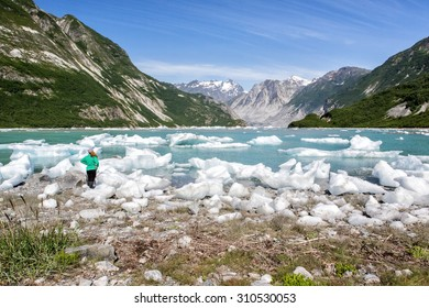 Woman admires ice and mountain beauty of McBride Inlet in Glacier Bay