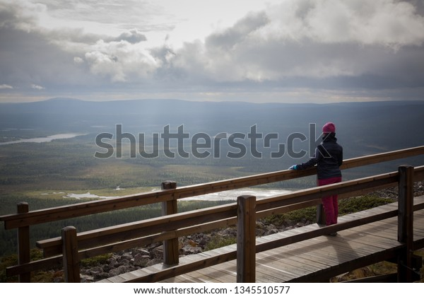 The woman admires summer scenery from the top of Levitunturi in Lapland, Finland