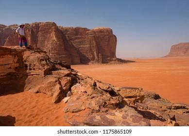 Woman admiring desert landscape from a rocky height. Wadi Rum, Jordan