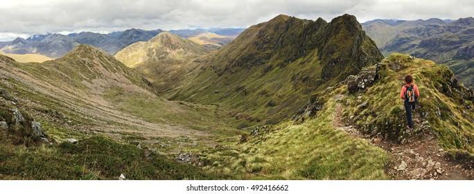 Woman admiring the notorious Aonach Eagach ridge in the Scottish Highland. Glencoe, Scotland, UK