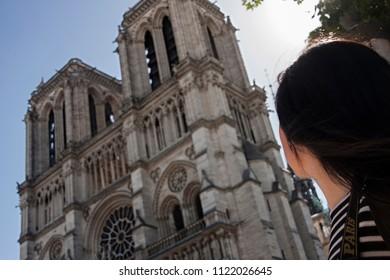 a woman is admiring notre dame facade in paris