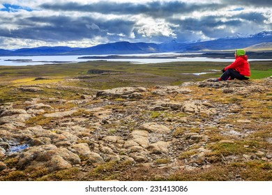 A woman admiring the view from the top of Helgafell Mountain in western Iceland