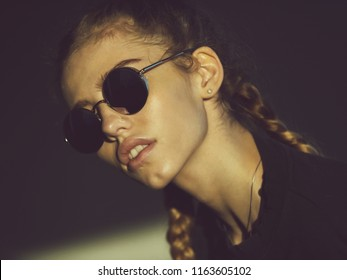woman or adorable girl with pretty face and two plaits, braid hair in fashionable, metallic sunglasses with blue lenses posing on grey background. Fashion, accessory