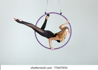 Woman aerial acrobat performs with tricks on the hula hoop at the top.