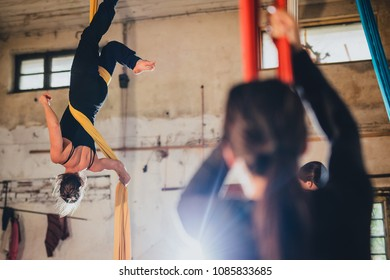A woman aerial gymnastic dancer on silk rope performing in an industral environment of an abandoned workshop or warehouse.