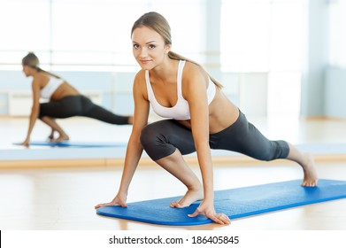 Woman in aerobics class. Beautiful young woman in sports clothing exercising and smiling