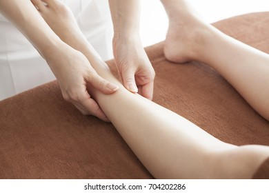 A woman aesthetician with a woman aiming for a beautiful leg with an esthetic salon.